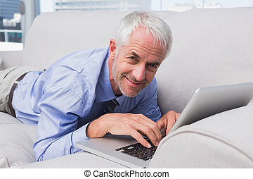 Businessman lying on couch using laptop and smiling at...