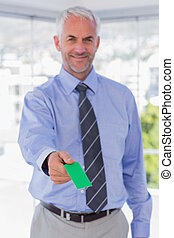 Happy businessman giving green business card in his office