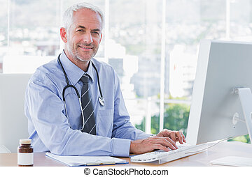 Doctor typing and using his computer in the office