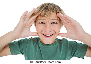 Surprised boy smiling with hands raised on white background