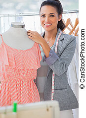 Smiling fashion designer adjusting dress on a mannequin