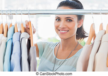 Smiling fashion designer looking at clothes in her studio