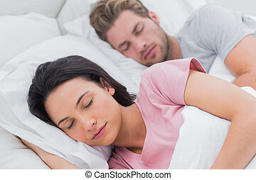 Portrait of a beautiful couple sleeping in bed