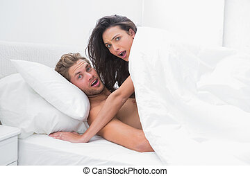 Couple surprised in bed - Embarrassed couple surprised in...