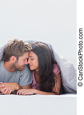 Beautiful couple head against head under the duvet in bed