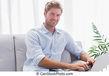 Man using his laptop sat on the couch in the living room