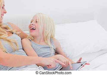 Mother and daughter laughing while using a tablet in bed