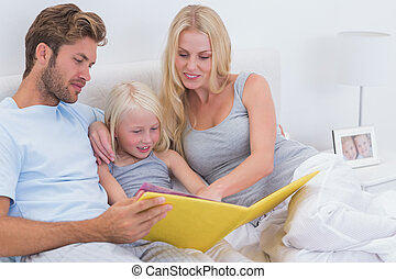 Beautiful couple reading a story to daughter in bed