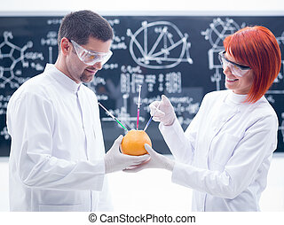 laboratory grapefruit experiment - close-up of two people in...