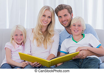 Portrait of a family holding a story book on the couch