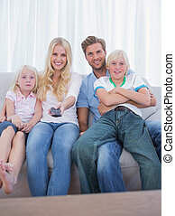 Parents and children watching TV in the living room