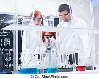 chemistry laboratory experiments - close-up of two women...