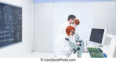people studying in a chemistry lab - side- view of a...