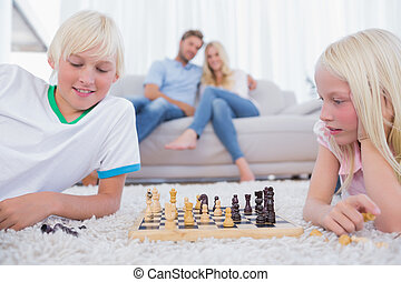 Children playing chess in the living room