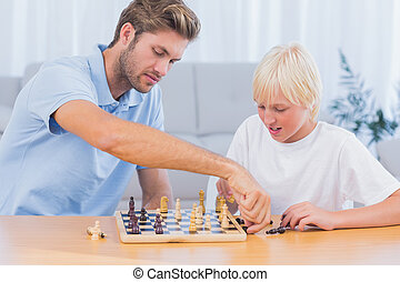 Father and his son playing chess in living room
