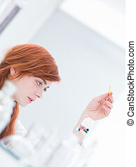 laboratory pills examination - close-up of woman in a...