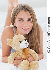 Young girl holding a teddy bear laid on her bed