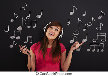 Happy woman listening to music through headphones
