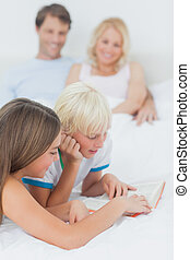 Siblings reading a book on the bed