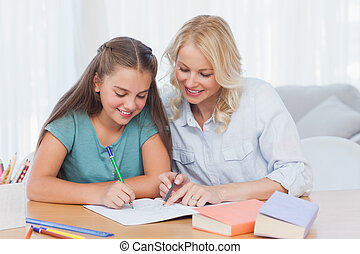 Smiling mother helping daughter with homework
