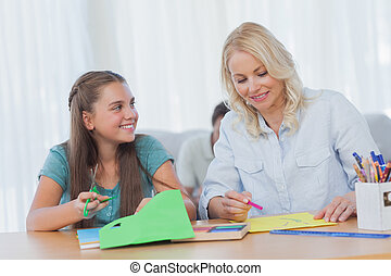 Mother doing arts and crafts with her daughter at home in...