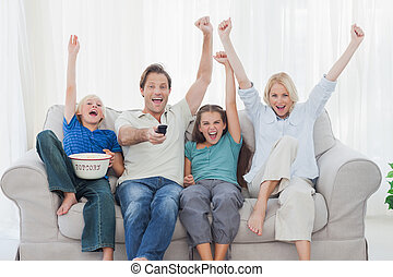Family watching television and raising arms while holding...