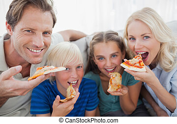 Smiling family eating pizza and looking at camera