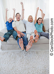 Portrait of a family watching television and raising arms...