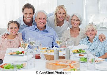 Extended family smiling at dinner family - Extended family...