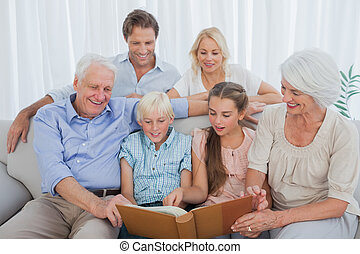 Extended family looking at an album photo in the living room