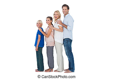Family posing together and looking at camera on white...
