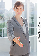 Businesswoman with hand out for handshake