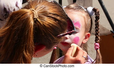 artist paints on face of little girl