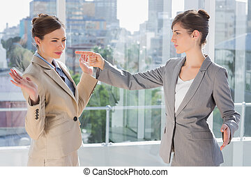 Annoyed businesswoman pointing at her rival in a bright...