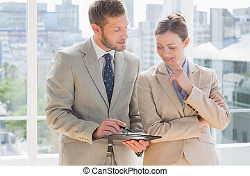 Business partners going over document on clipboard