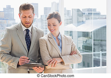 Smiling business partners going over document on clipboard