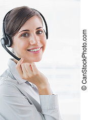 Call centre agent smiling at the camera in an office