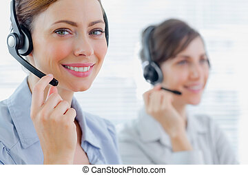 Smiling call centre agents with headsets at work in an...