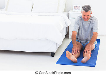 Man working out on an mat in his bedroom