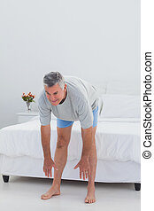Mature man working out in his bedroom
