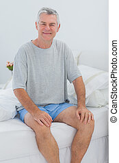 Cheerful man sitting in bed - Cheerful mature man sitting in...
