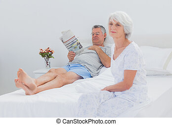 Mature woman sitting on bed while husband is reading a...