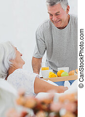 Man bringing wife breakfast in bed with orange juice and a...