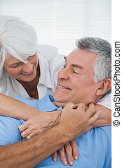 White haired woman hugging husband on the couch at home