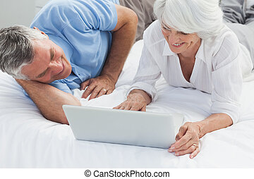 Cheerful couple using a laptop in bed