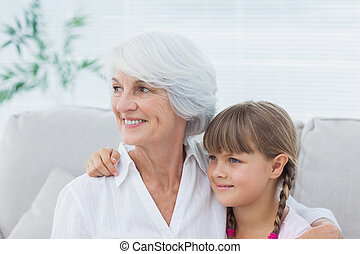Cute girl and grandmother sitting on the couch
