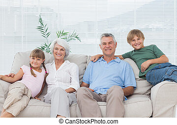Grandparents and grandchildren sitting on couch in the...