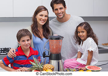 Family posing with a blender in the kitchen