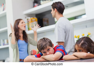 Couple arguing behind their children in the kitchen