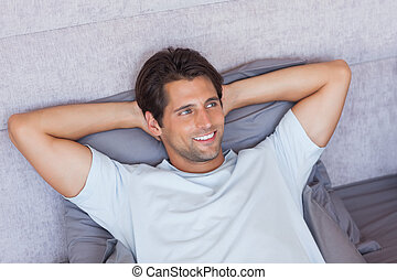 Handsome man lying in his bed at home